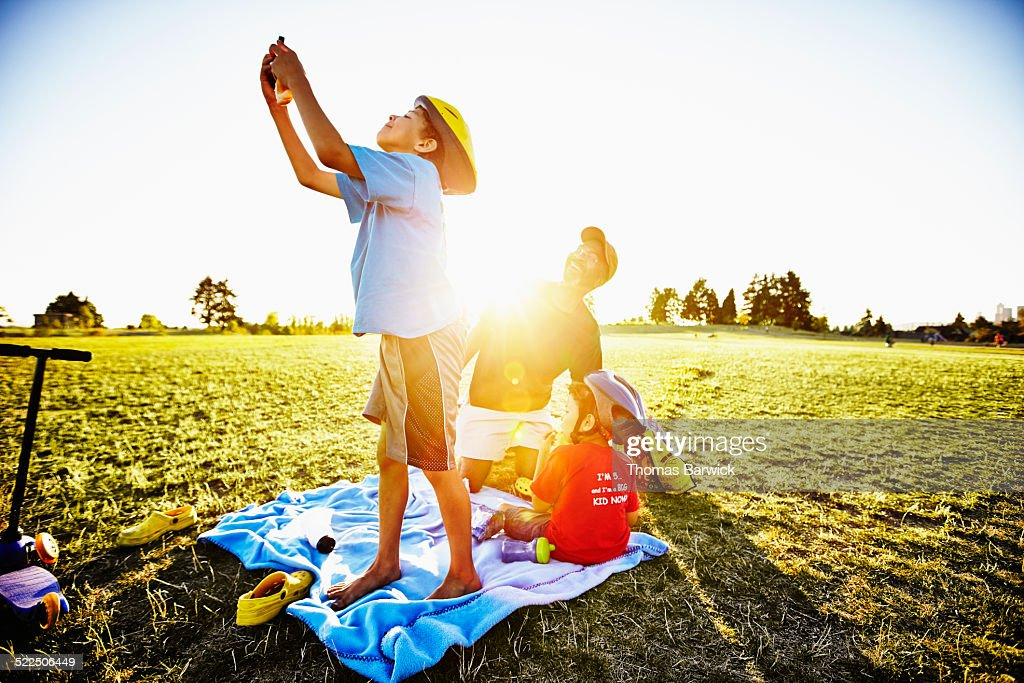 Smiling father and two young sons having picnic in park on grass field on summer evening son taking self portrait with smartphone