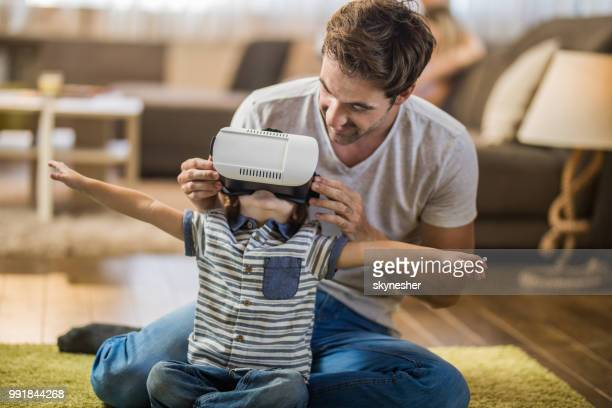 Smiling father assisting his small son with VR headset at home.