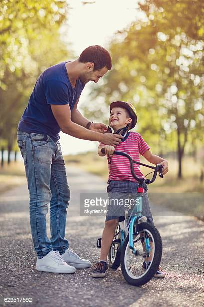 Smiling father assisting his son with cycling helmet in nature.