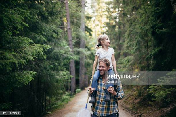 smiling father carrying daughter on shoulder while walking in forest - three quarter length stock pictures, royalty-free photos & images