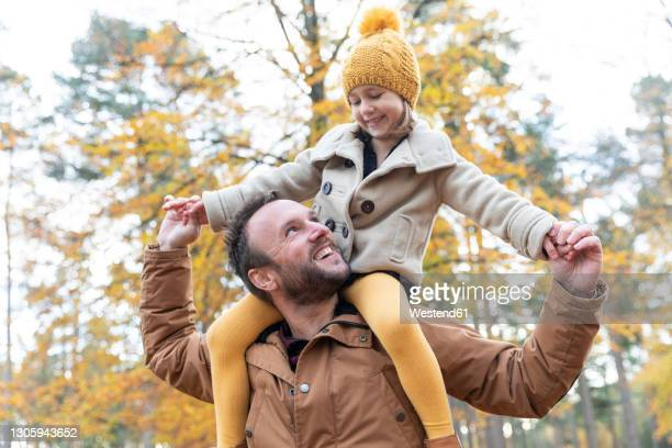smiling father carrying daughter on shoulders while standing in forest - daughter stock pictures, royalty-free photos & images