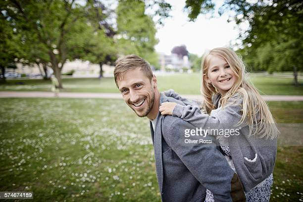 Smiling father carrying daughter piggyback