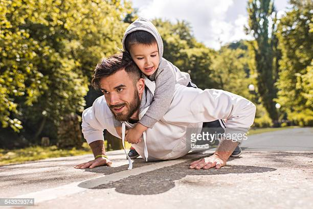 Smiling father doing push-ups with his little boy in nature.