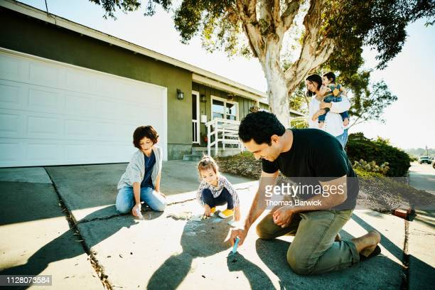 Smiling father drawing chalk pictures on driveway with daughters