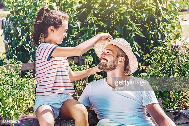 smiling father fooling around with teenage daughter in summer garden