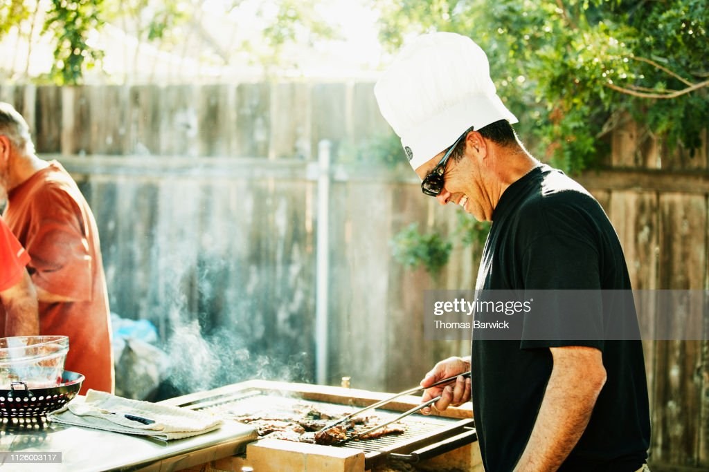 Smiling father grilling in backyard during family barbecue : Stockfoto