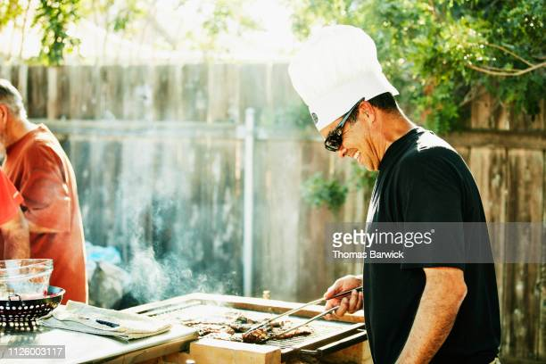 smiling father grilling in backyard during family barbecue - genot stockfoto's en -beelden