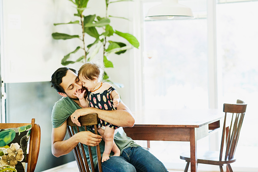 Smiling father holding and kissing infant daughter in dining room in home - gettyimageskorea
