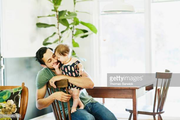 smiling father holding and kissing infant daughter in dining room in home - genderblend stock-fotos und bilder