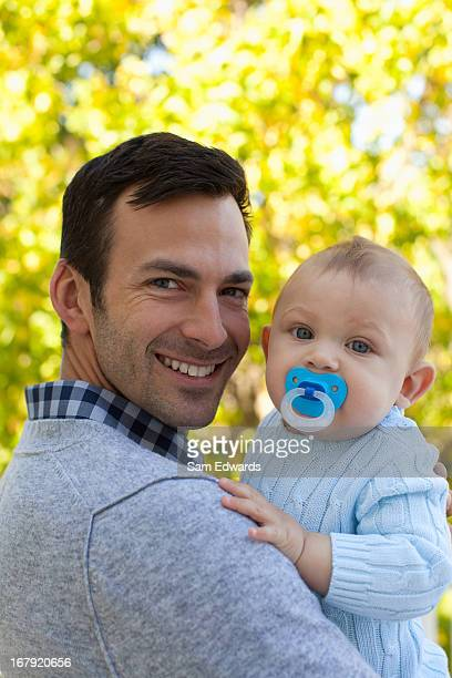 Smiling father holding baby outdoors