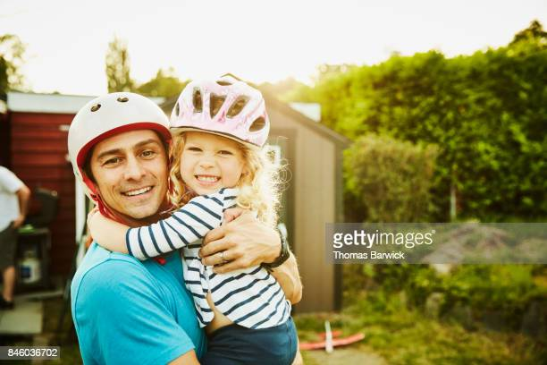 Smiling father holding daughter after riding bikes on summer evening