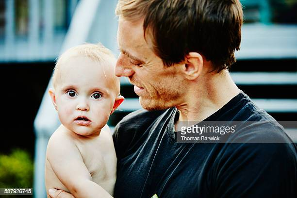 Smiling father holding infant daughter in backyard
