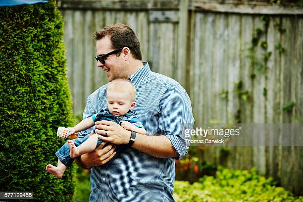 Smiling father holding infant son during party