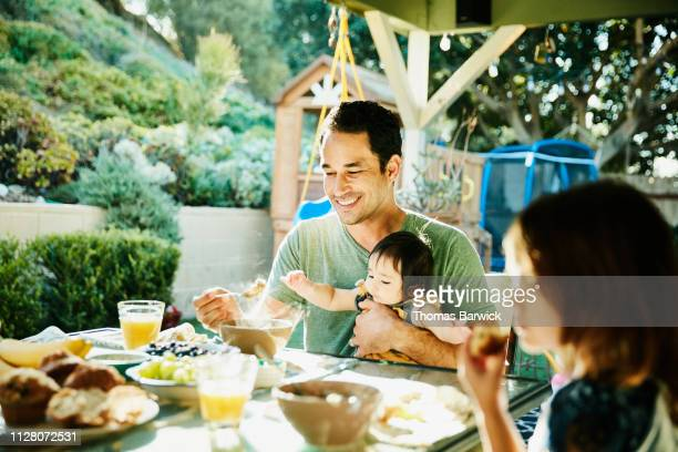 Smiling father holding infant son while enjoying breakfast with family at table in backyard
