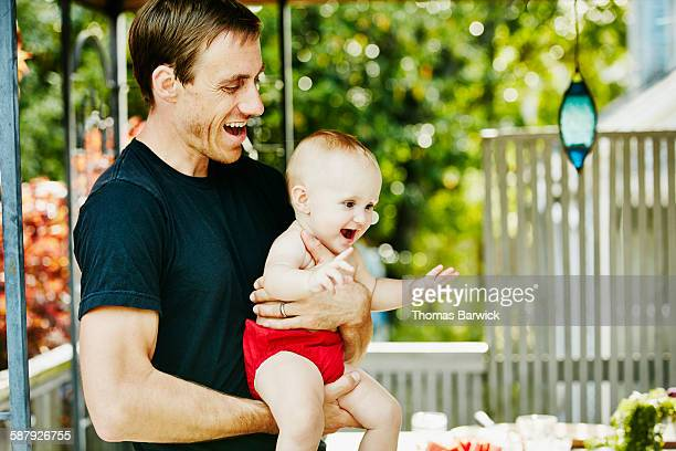 Smiling father holding laughing infant daughter