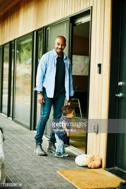 smiling father holding toddler daughters hand while walking through doorway - fully unbuttoned stock pictures, royalty-free photos & images
