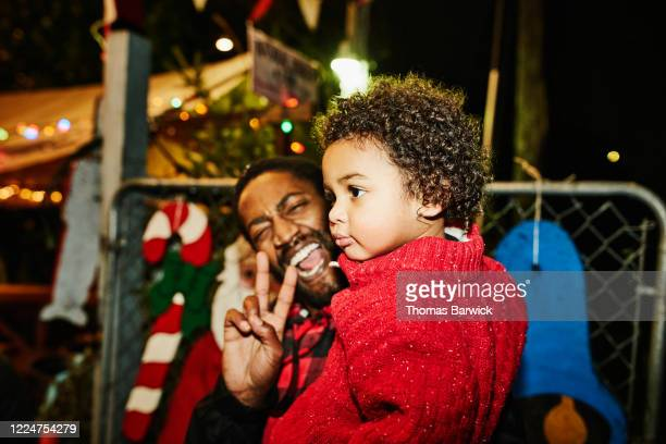 smiling father holding toddler son while shopping for christmas tree - genderblend stock pictures, royalty-free photos & images