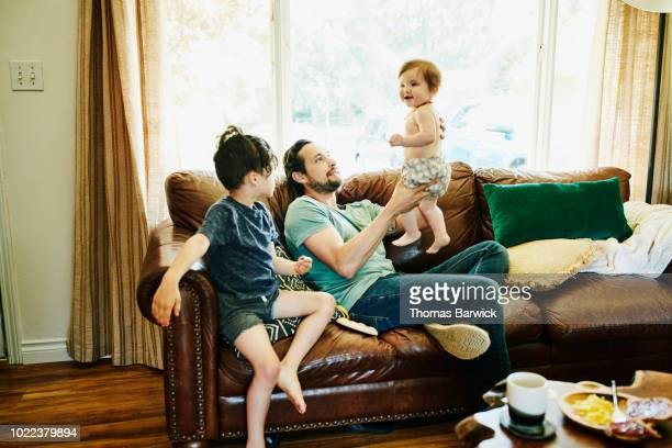 Smiling father holding up infant daughter while hanging out with children in living room