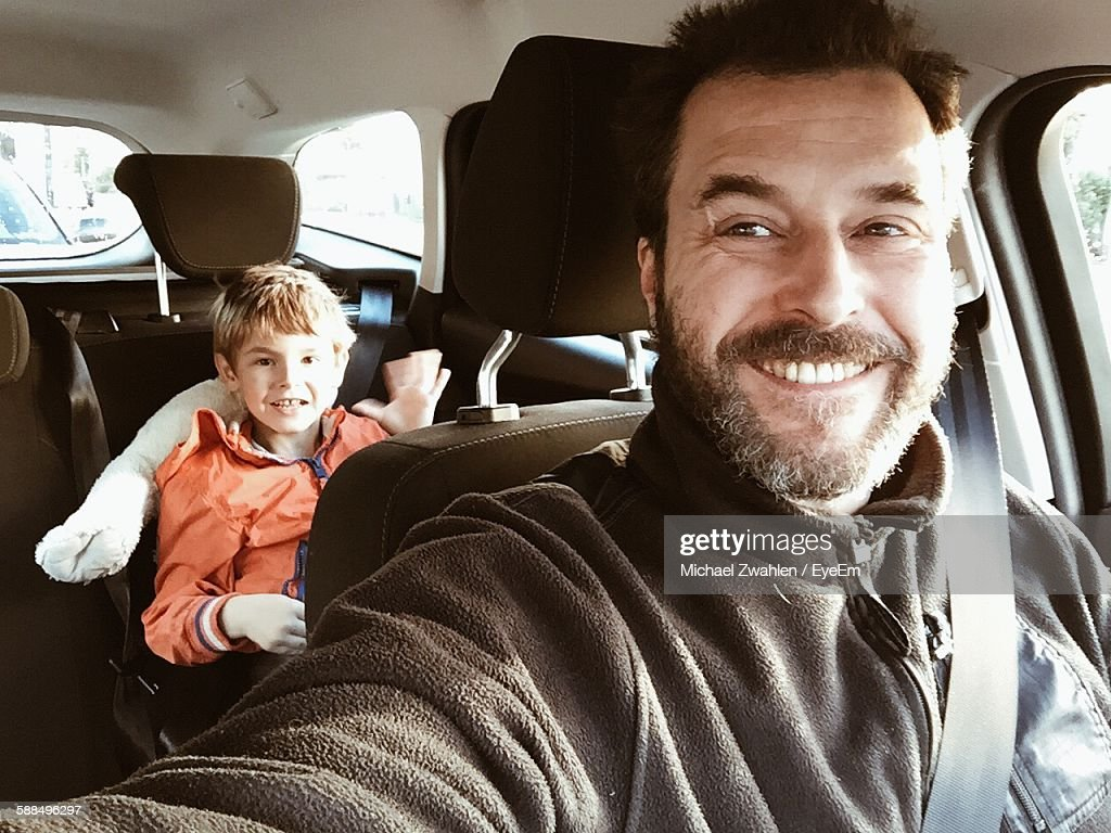 Smiling Father In Car With Son Sitting At Back Seat : Stock Photo