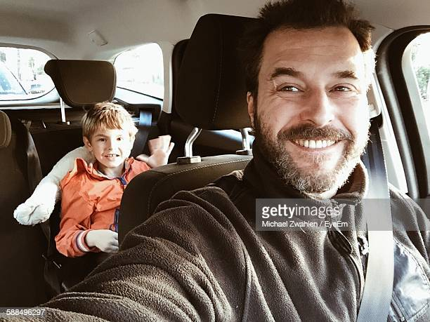 smiling father in car with son sitting at back seat - uomini di età media foto e immagini stock