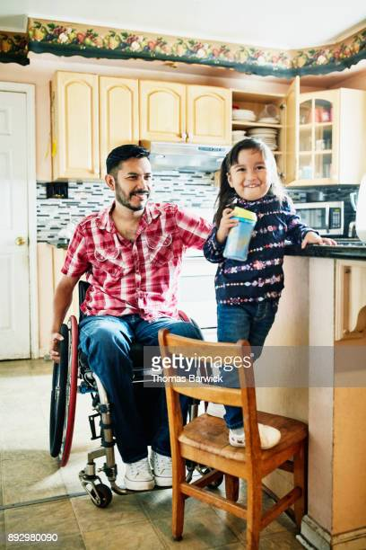 Smiling father in wheelchair hanging out with daughter in kitchen after making snack