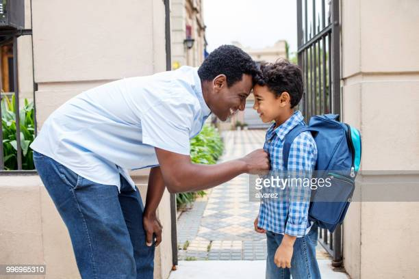 smiling father leaving son with backpack to school - first day of school stock pictures, royalty-free photos & images