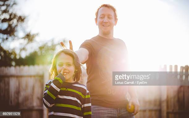 smiling father making peace sign behind son in yard on sunny day - padre single foto e immagini stock