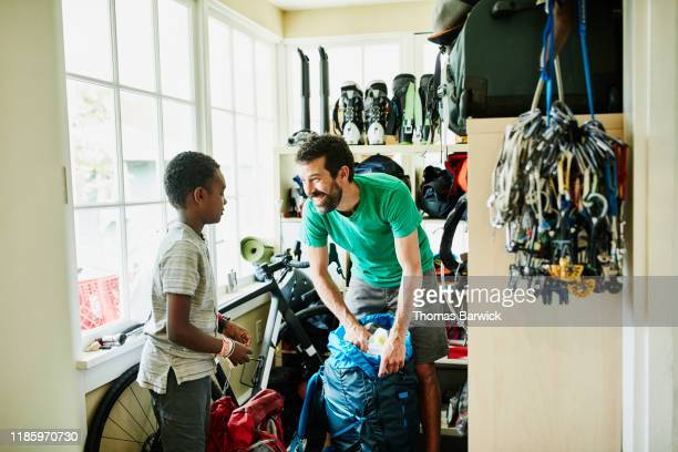 smiling father packing backpack with son in gear room in home - 黄緑色 ストックフォトと画像