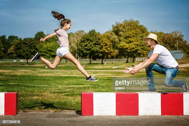 smiling father playing with jumping teenage daughter in park