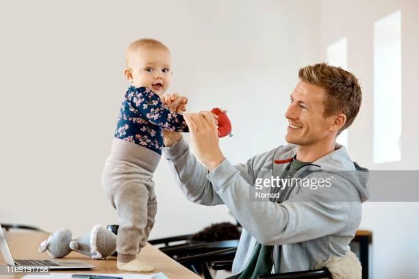 lachende vader spelen met zoon thuis - onschuld stockfoto's en -beelden