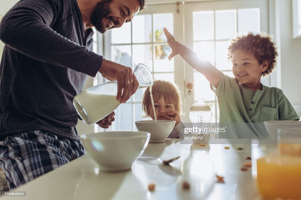 Smiling father pouring milk in to bowls for breakfast : Stock Photo