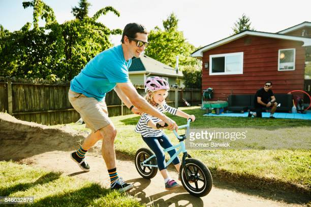 Smiling father pushing young daughter on bike on dirt track in backyard on summer afternoon