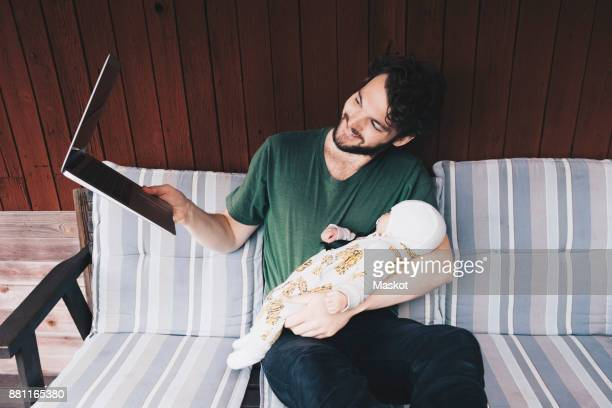 Smiling father showing baby boy in video conference on laptop while sitting at holiday villa