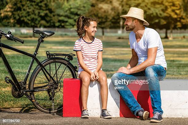 smiling father sitting with teenage daughter in park - fille de 12 ans photos et images de collection