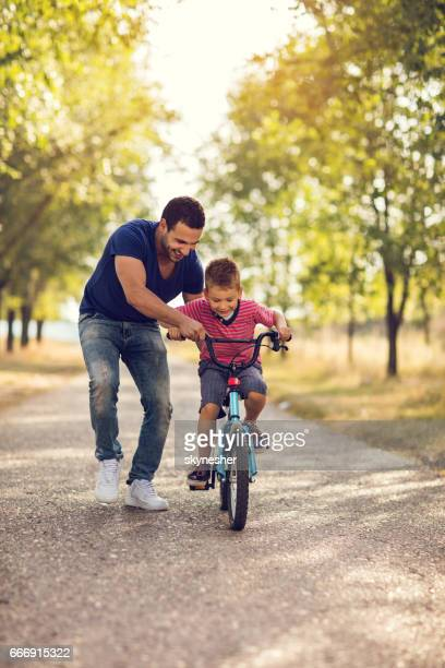 smiling father teaching his son to ride bicycle in nature. - montar imagens e fotografias de stock