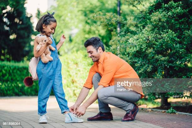 smiling father tying shoelaces of her daughter in the park - school girl shoes stock pictures, royalty-free photos & images