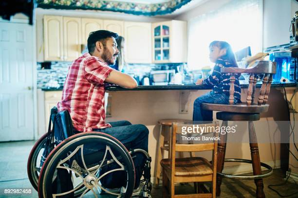Smiling father using a wheelchair in discussion with young daughter while sitting together at kitchen counter.