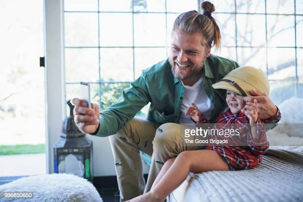 Smiling father using mobile phone to take selfie with daughter