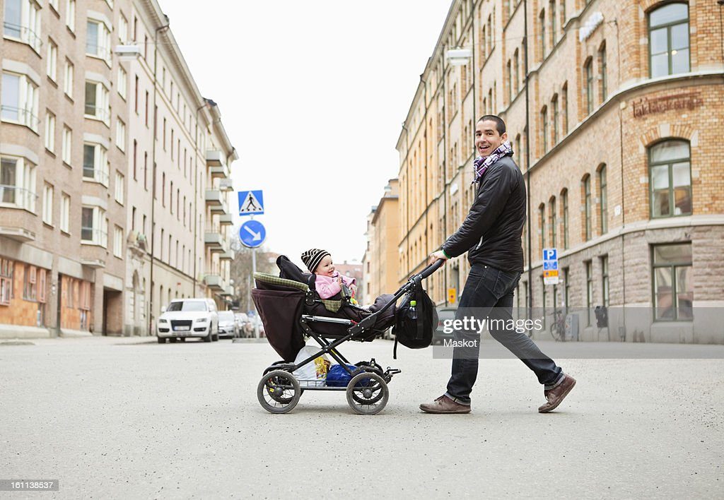 Smiling father walking with cute baby (0-11 months) in stroller : Stock Photo
