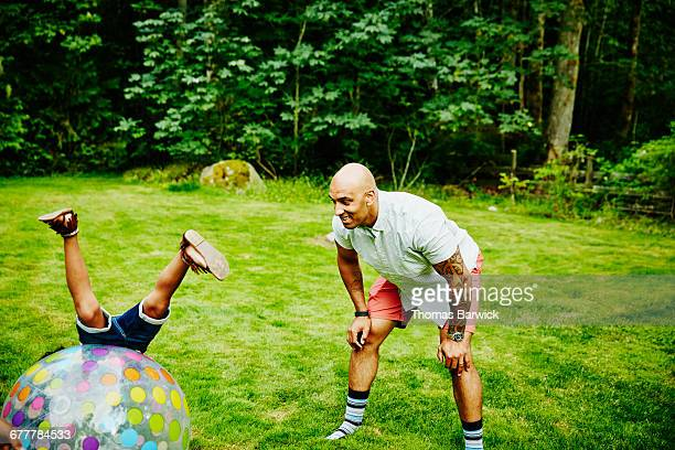 Smiling father watching daughter roll over ball