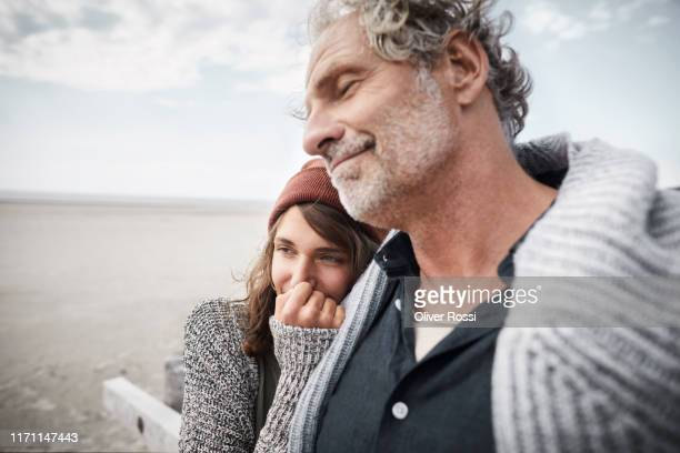 smiling father with adult daughter on the beach - schleswig holstein stock pictures, royalty-free photos & images