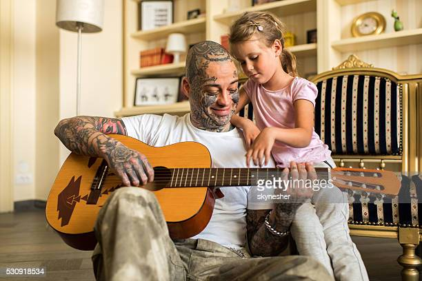 Smiling father with daughter playing acoustic guitar at home.