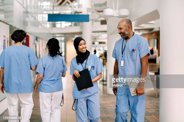 smiling female and male colleagues with file talking while walking in hospital - hoofddeksel stockfoto's en -beelden