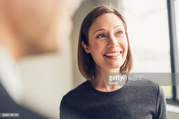 smiling female architect looking away in office - looking away stock pictures, royalty-free photos & images