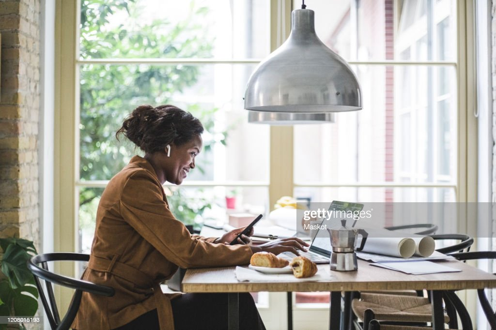 Smiling female architect using phone while sitting at home office : Stock Photo