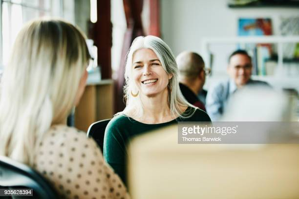 Smiling female architect working with colleague at workstation in office