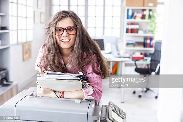 smiling female assistant leaning on copy machine in workplace - part time job stock pictures, royalty-free photos & images