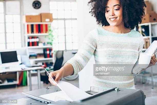 Sonriente mujer asistente con fotocopiadora en el trabajo