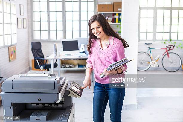 Smiling female assistant using copy machine in workplace