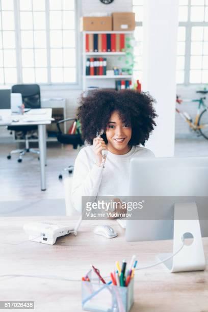Lächelnde Assistentin mit Festnetz-Telefon im modernen Büro